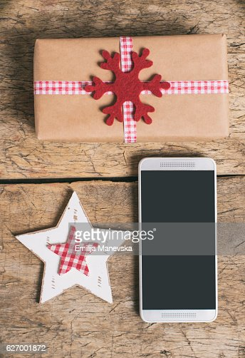 Smart phone and Christmas decoration on wooden table