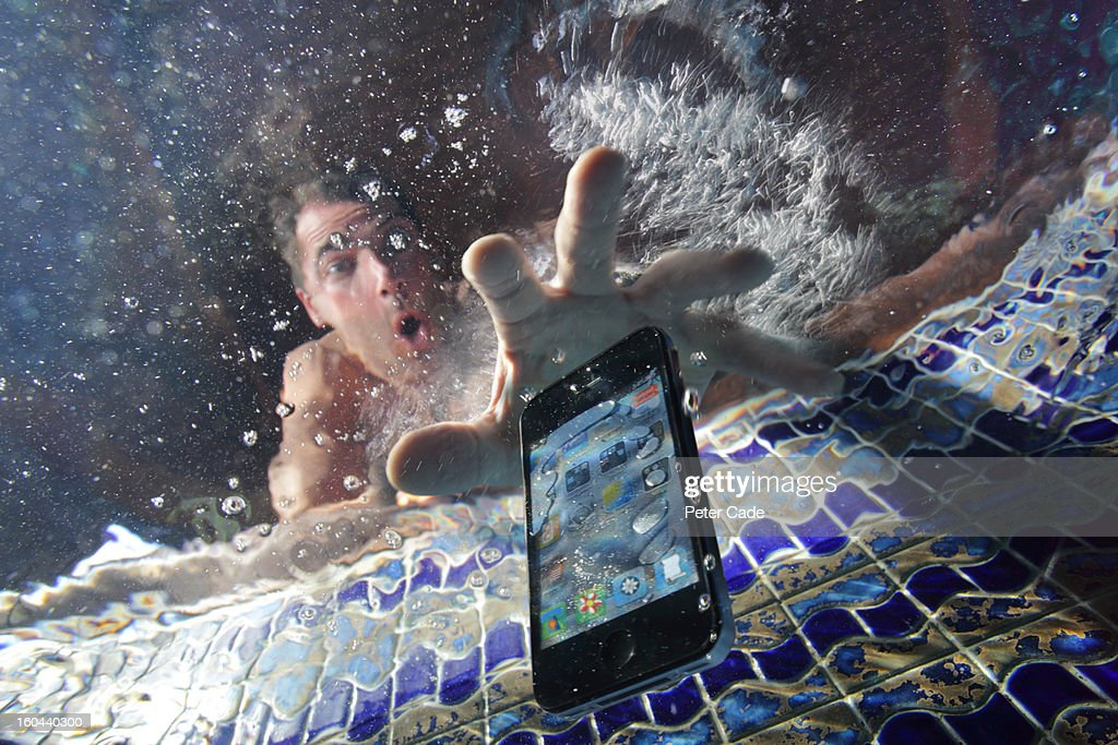 Smart phone being dropped into swimming pool : Stock Photo