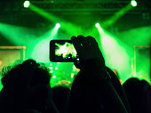 Detail of a hand holding a smart phone and filming a concert.