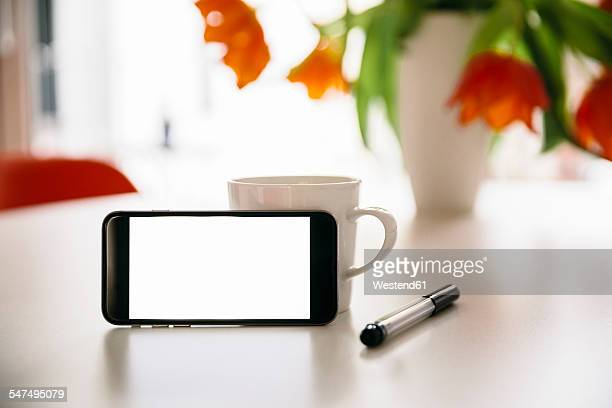 Smart phone leaning at a coffee cup on a white round table with red tulips
