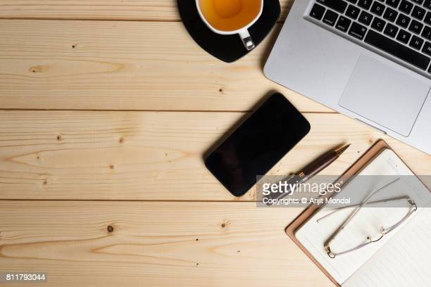 Smart phone on wooden office table top view shot with laptop keyboard