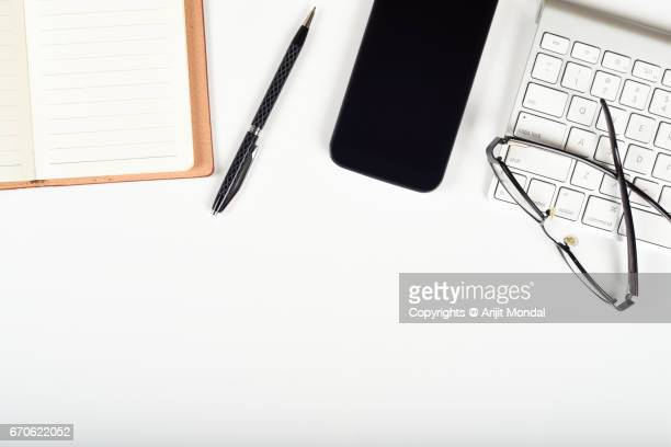 Smart Phone Top View with Notebook, Pen, Cropped Keyboard, Eyeglasses on White Table