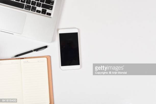 Smart phone white background simple office desk top view with Laptop