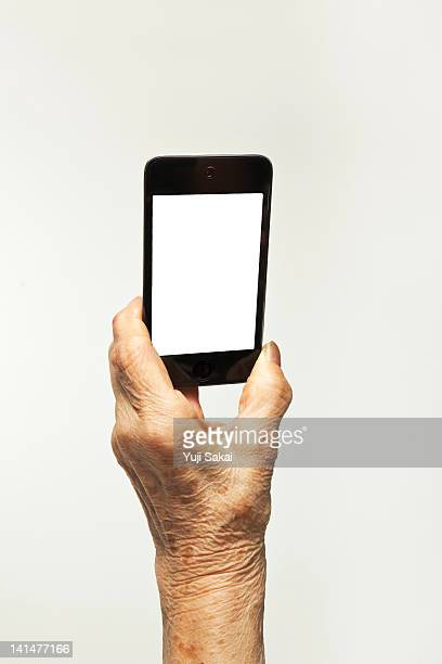 smart phone with  a hand of senior woman