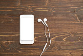 Smart phone with headphones on table