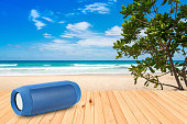 Smart phones and portable speaker on the beach.