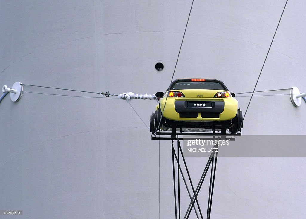 A Smart roadster car drives on high wires fixed on the TV tower in the southern town of Stuttgart 20 May 2004. The car, equipped with special wheel-rims, reclined a distance of 192 meters at the height of 53 meters.