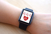 Smart watch displaying heart rate monitor on a woman wrist.