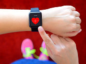 Runner using smart watch with heart rate application on a running track.