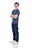 Studio shot of smart young boy standing with his arms crossed on white background
