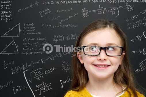 Smart young girl stood infront of a blackboard : Stock Photo