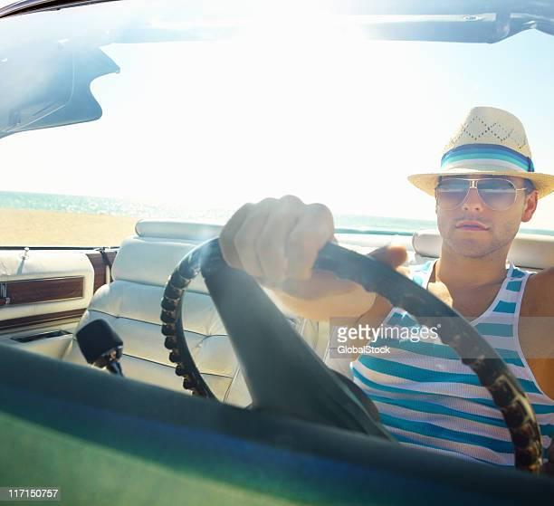 Intelligente giovane uomo che guida la sua auto convertibile sulla spiaggia