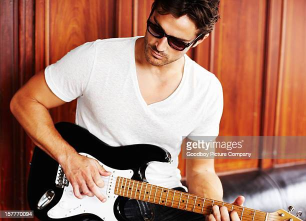 Smart young man in sunglasses playing a guitar
