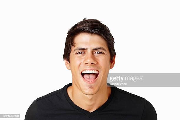 Élégant jeune homme criant avec joie contre blanc