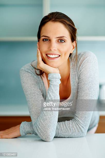 Smart young woman standing at the kitchen counter