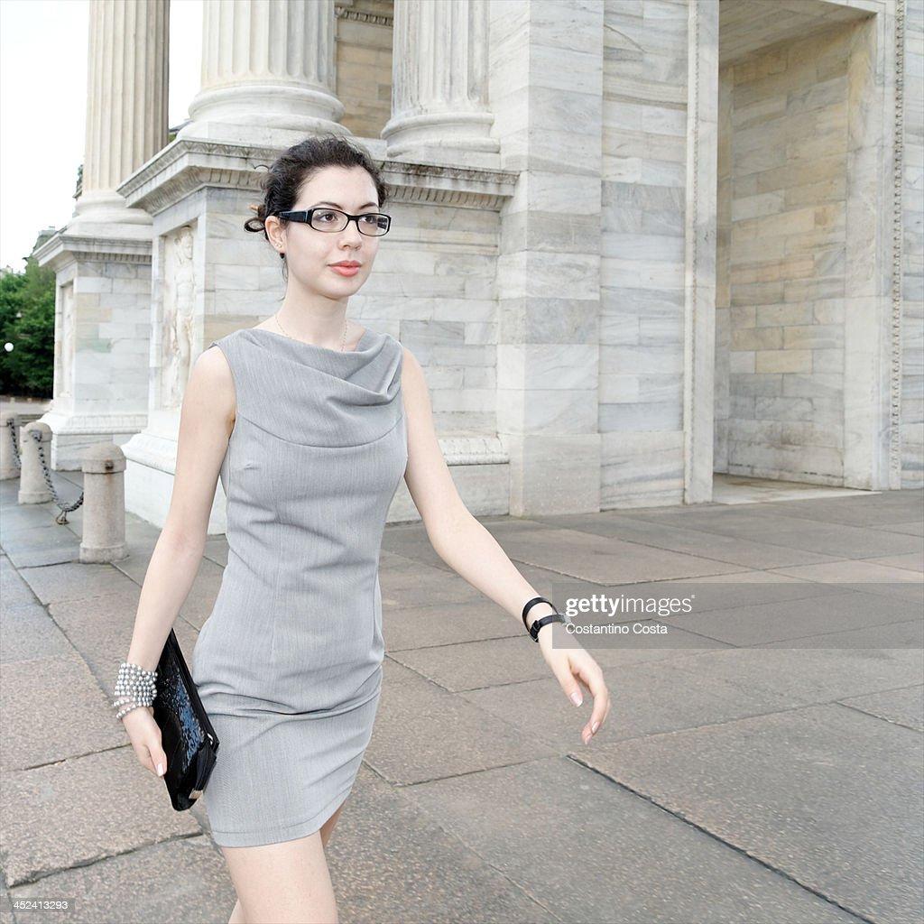 Smart young woman walking along pavement