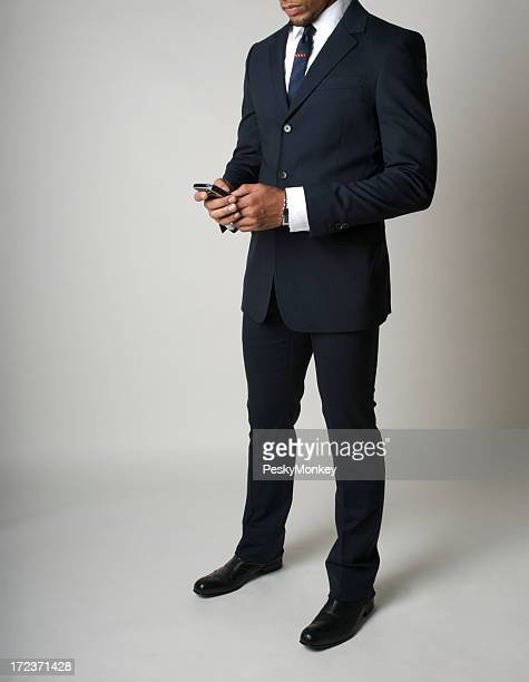 Smartly Dressed African American Businessman Checks His Smartphone