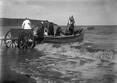 Smartly dressed family group being helped from a two wheeled cart into a coastal rowing boat on an English beach circa 1900
