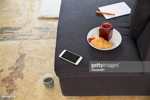 Smartphone and croissant with jam on couch