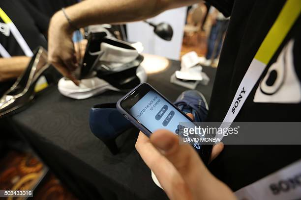 A smartphone app is used to automatically tighten Digisole smart shoes at The CES Unveiled press event January 4 2016 in Las Vegas Nevada ahead of...