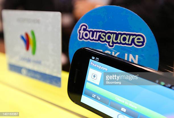 A smartphone displays Foursquare Technologies Inc branding beside a Google Inc Mobile Wallet card stand on display at the Mobile World Congress in...