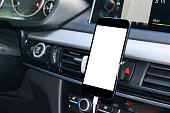 Smartphone in a car use for Navigate or GPS. Driving a car with Smartphone in holder. Mobile phone with isolatede white screen. Blank empty screen. copy space. Empty space for text. modern car interio