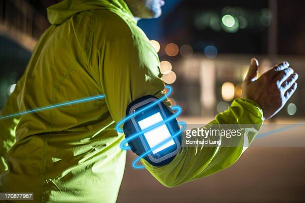 Smartphone of Runner surrounded by light trails