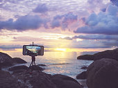 Close up smartphone on stand mobile tripod take sunset landscape photo and video time lapse at summer beach.