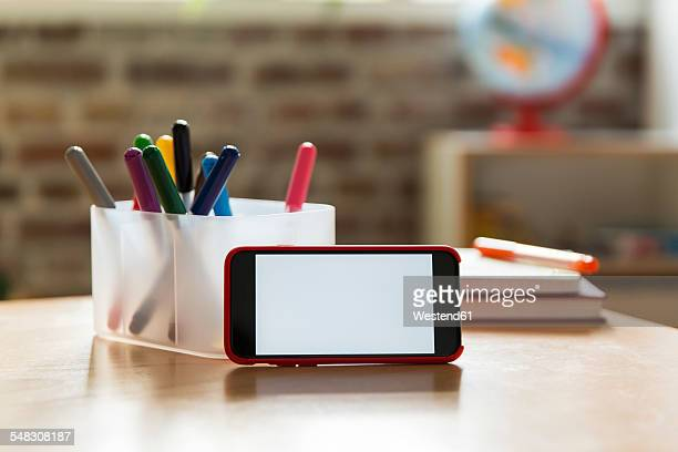 Smartphone on wooden table in childrens room