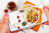 Female hands with smart phone taking photo of bulgur salad. Mobile shot food photo