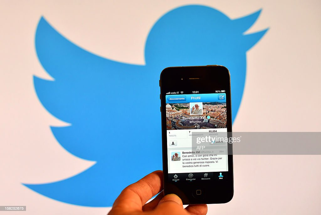 A smartphone showing the first twitter message of Pope Benedict XVI in Italian is held in front of a computer showing the logo of Twitter on December 12, 2012 in Rome. Pope Benedict XVI sent his first Twitter message from a digital tablet on Wednesday during his weekly general audience using the handle @pontifex, blessing his hundreds of thousands of new Internet followers.