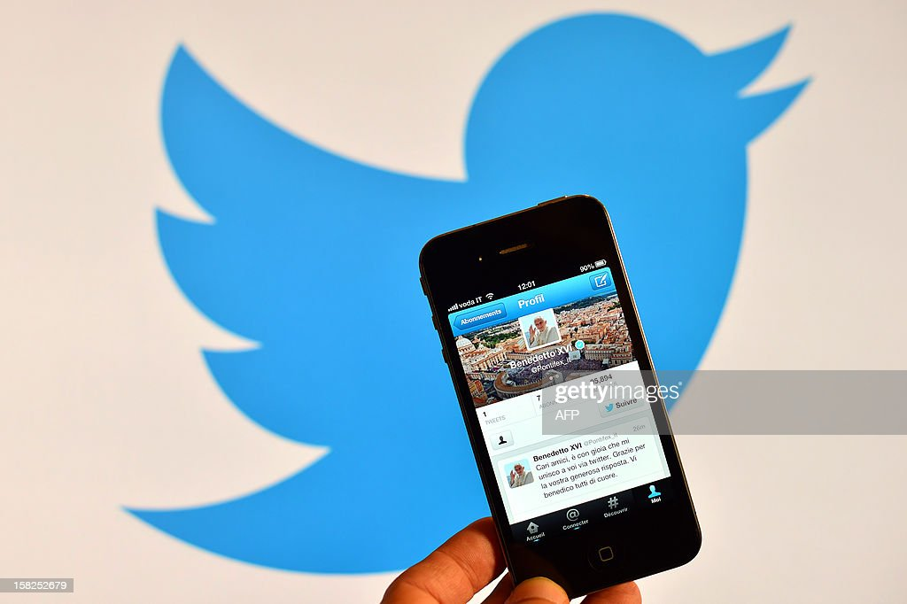A smartphone showing the first twitter message of Pope Benedict XVI in Italian is held in front of a computer showing the logo of Twitter on December 12, 2012 in Rome. Pope Benedict XVI sent his first Twitter message from a digital tablet on Wednesday during his weekly general audience using the handle @pontifex, blessing his hundreds of thousands of new Internet followers. AFP PHOTO / GABRIEL BOUYS