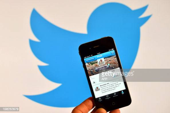 A smartphone showing the first twitter message of Pope Benedict XVI in Italian is held in front of a computer showing the logo of Twitter on December...