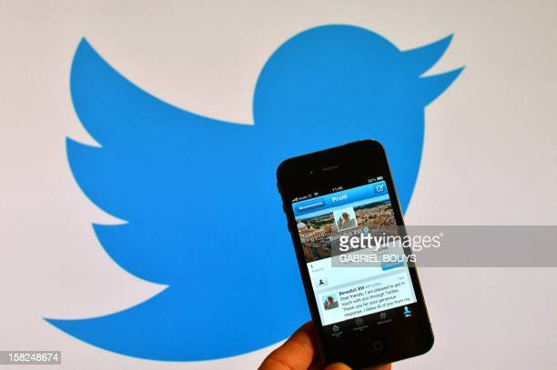 A smartphone showing the first twitter message of Pope Benedict XVI is held in front of a computer showing the logo of Twitter on December 12 2012 in...