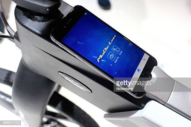 A smartphone sits in the frame of a Ford MoDeMe foldable electric ebike in the Ford Motor Co pavilion at the Mobile World Congress in Barcelona Spain...