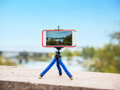 smart phone stands on a tripod and takes a panorama of nature