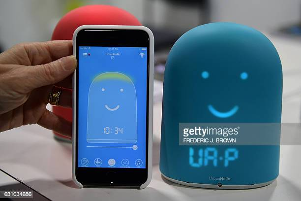A smartphone used to control the device is placed next to Remi the smart alarm clock for kids which offers a night tracker a sleep trainier and a...
