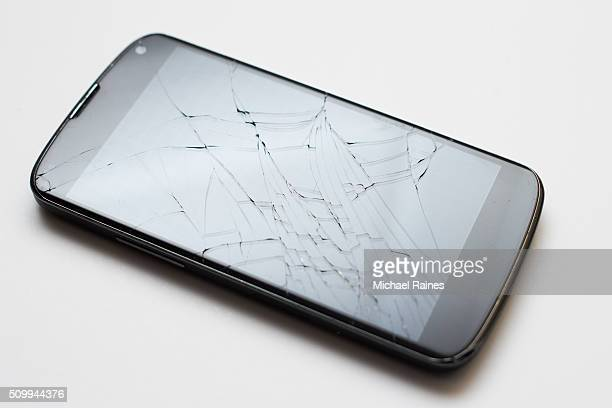 Smartphone with cracked screen on white background