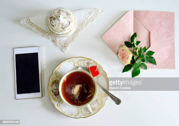 Smartphone with cup of tea and flower seen from above