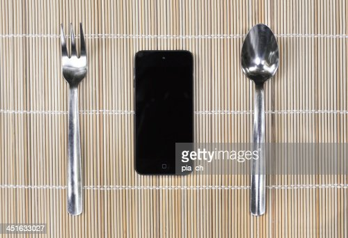 Smartphone with fork and spoon on bamboo mat background : Stock Photo