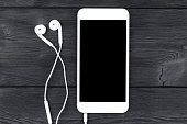 Smartphone with headphones on black wooden table. Smartphone with solated screen. Empty space for text. Copy space. Smartphone blank screen. Smartphone mock up. earphone.