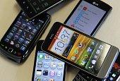 Smartphones / Handys verschiedener Herstelelr liegen auf einem Tisch