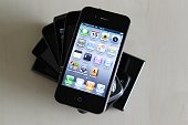 Smartphones / Handys verschiedener Herstelelr liegen auf einem Tisch oben ein Apple iPhone 4
