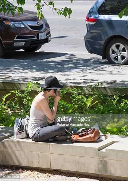 Smartphones in everyday life Trendy cool hipster woman with phone and hat Sitting on the curb and looking at the mobile phone