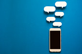 Smartphones with paper speech bubbles on blue background. Communication concept. Top view. Copy space. Paper composition