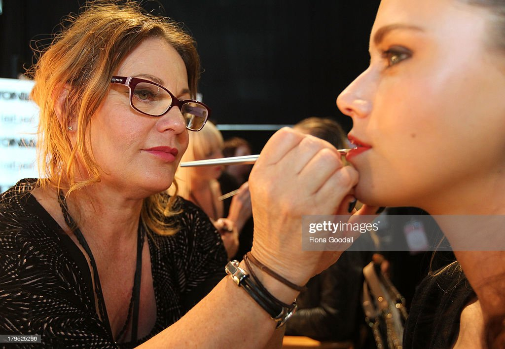 Smashbox makeup artist Michelle Devereux prepares model Gabrielle Carter ahead of the Tiger Lilly show during New Zealand Fashion Week at the Viaduct Events Centre on September 5, 2013 in Auckland, New Zealand.