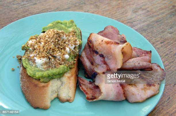 Smashed avocado, crumbled feta cheese and dukkah on toasted sourdough bread with a side of fried bacon