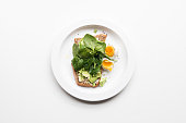 High angle view of smashed avocado, spinach on toast with boiled egg