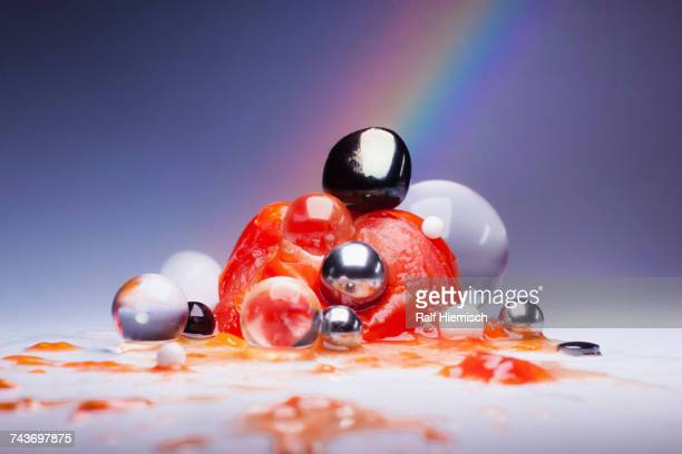Smashed tomato over shiny marbles and spheres against multi colored background