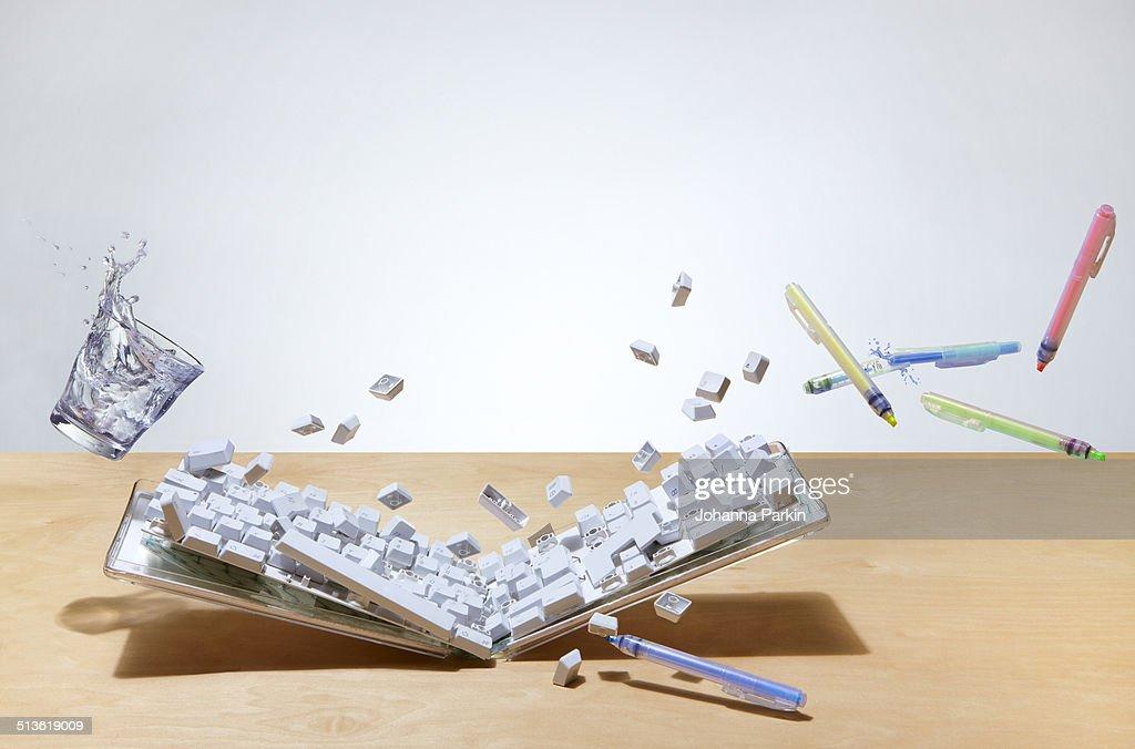 Smashed up computer keyboard on office desk